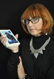 Marcia O'Hara in a black turtleneck holding image of Awakening Aeon Tarot Deck